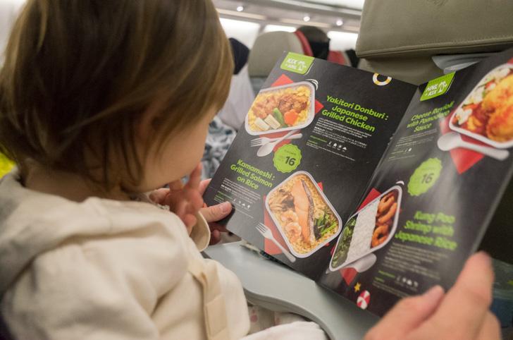 機内食パンフレットを見る子供